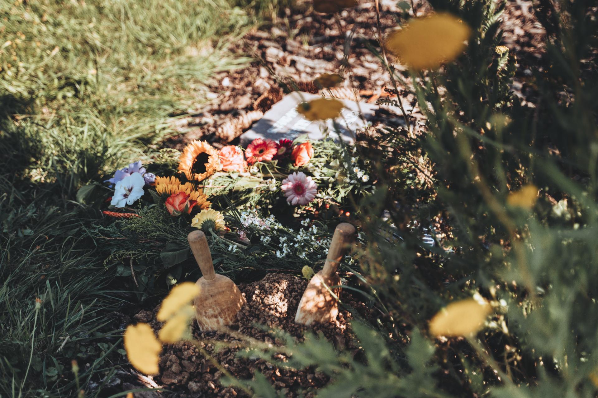 Miesto po uložení popola v kvetinovom záhone.